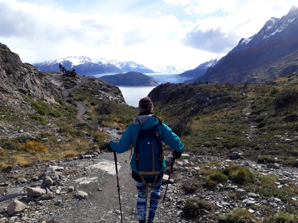 A person walking with hiking sticks and a backpack. Mountains and a lake in the background