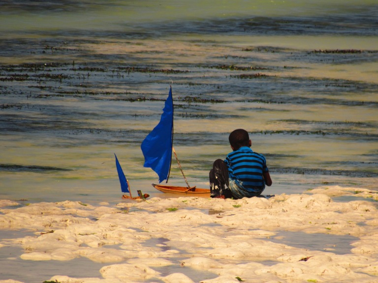 Kid playing with a blue boat on Jambiani Beach in Zanzibar, Tanzania