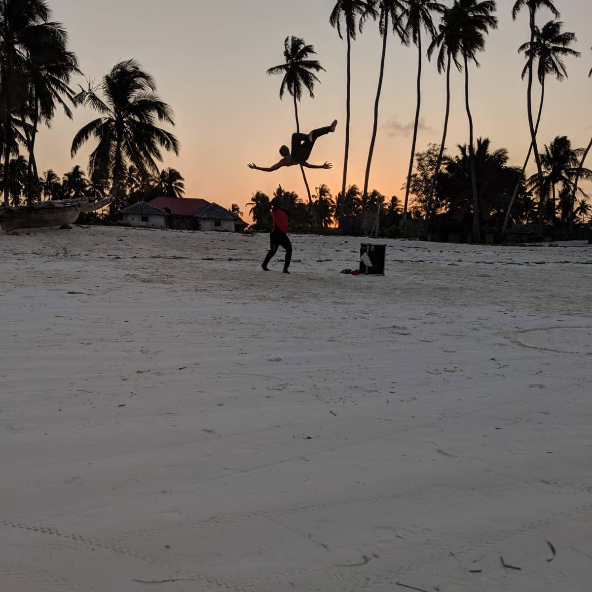 People training an acrobatic routine at sunset on Jambiani Beach, Zanzibar