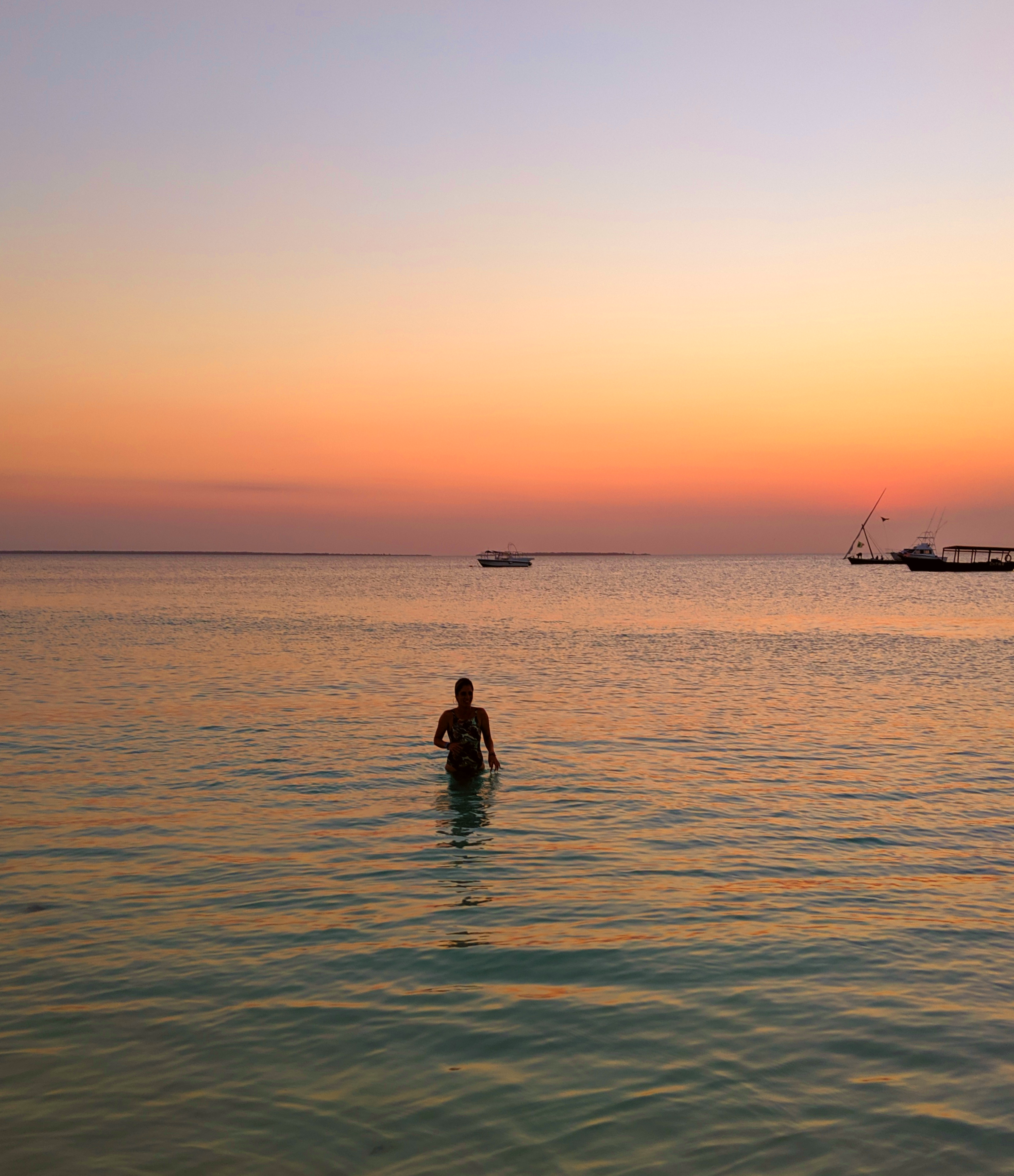 A person sea swimming at sunset