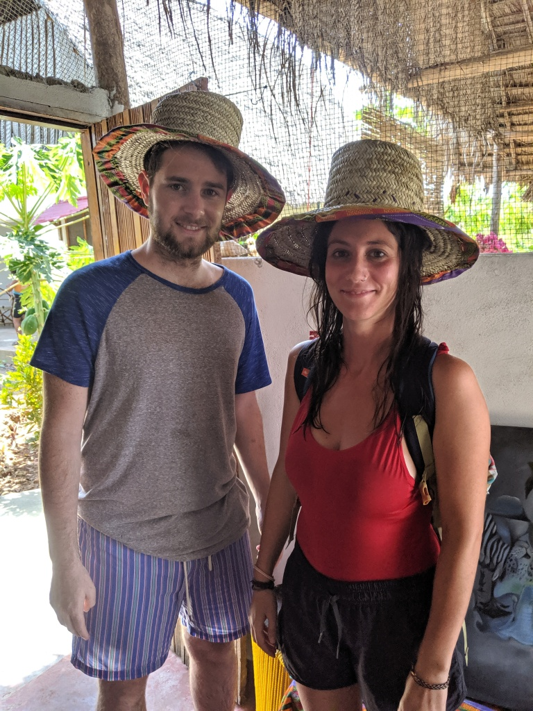 Two people standing with hats