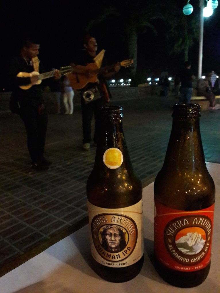 Two bottles of Peruvian beer on ta table and musicians playing in the background
