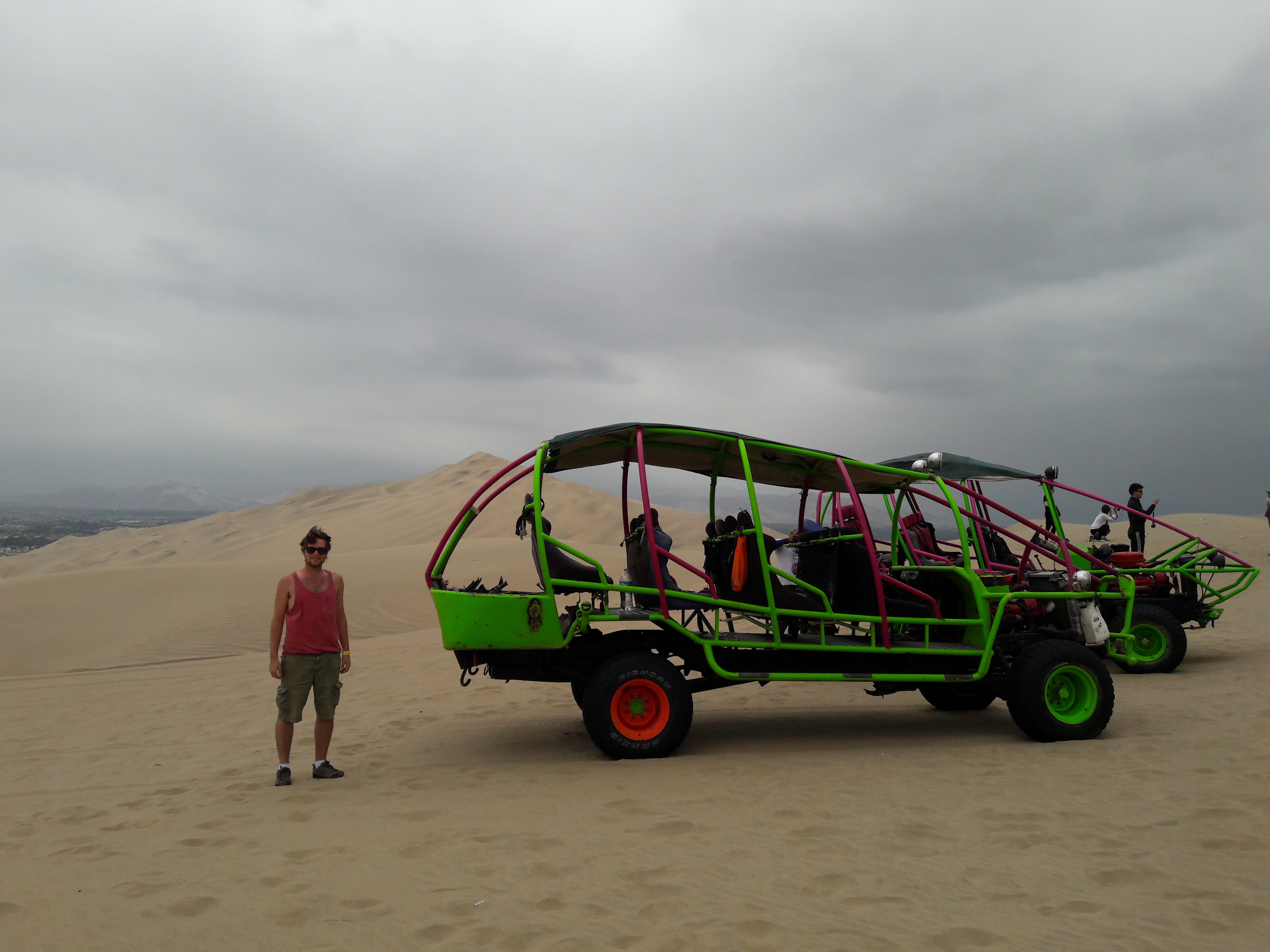 A man standing beside a dune buggy in Huacachina