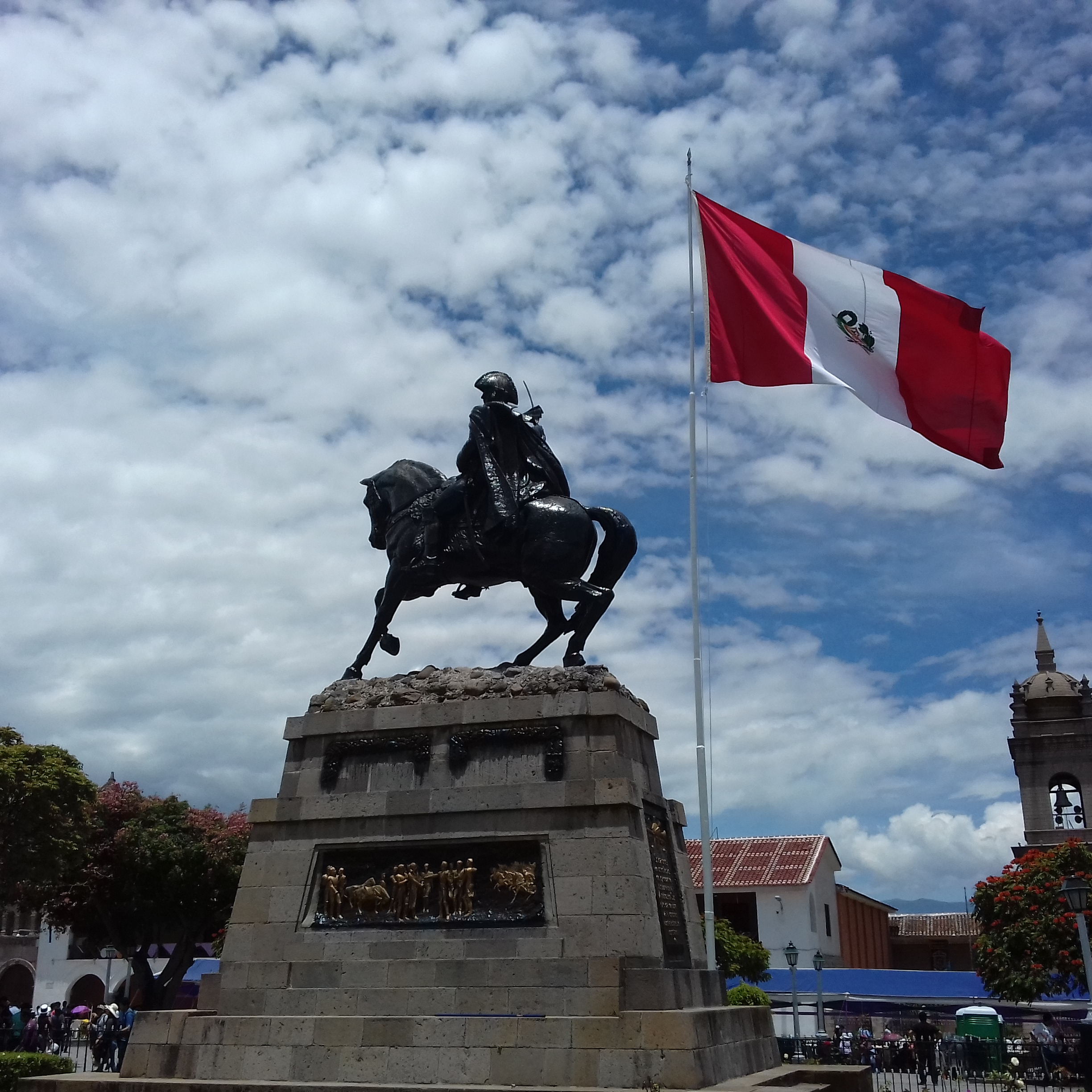 astatue of a man on a horse and a Peruvian flag