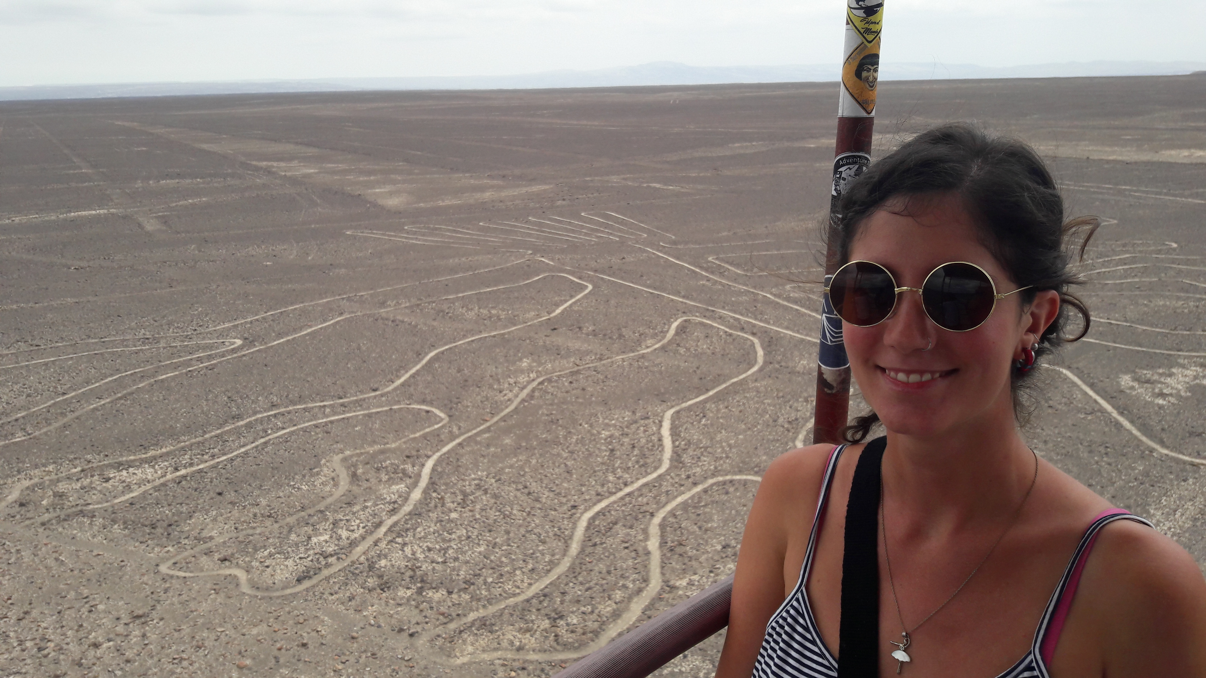 lines in the sand and a woman smiling with sunglasses