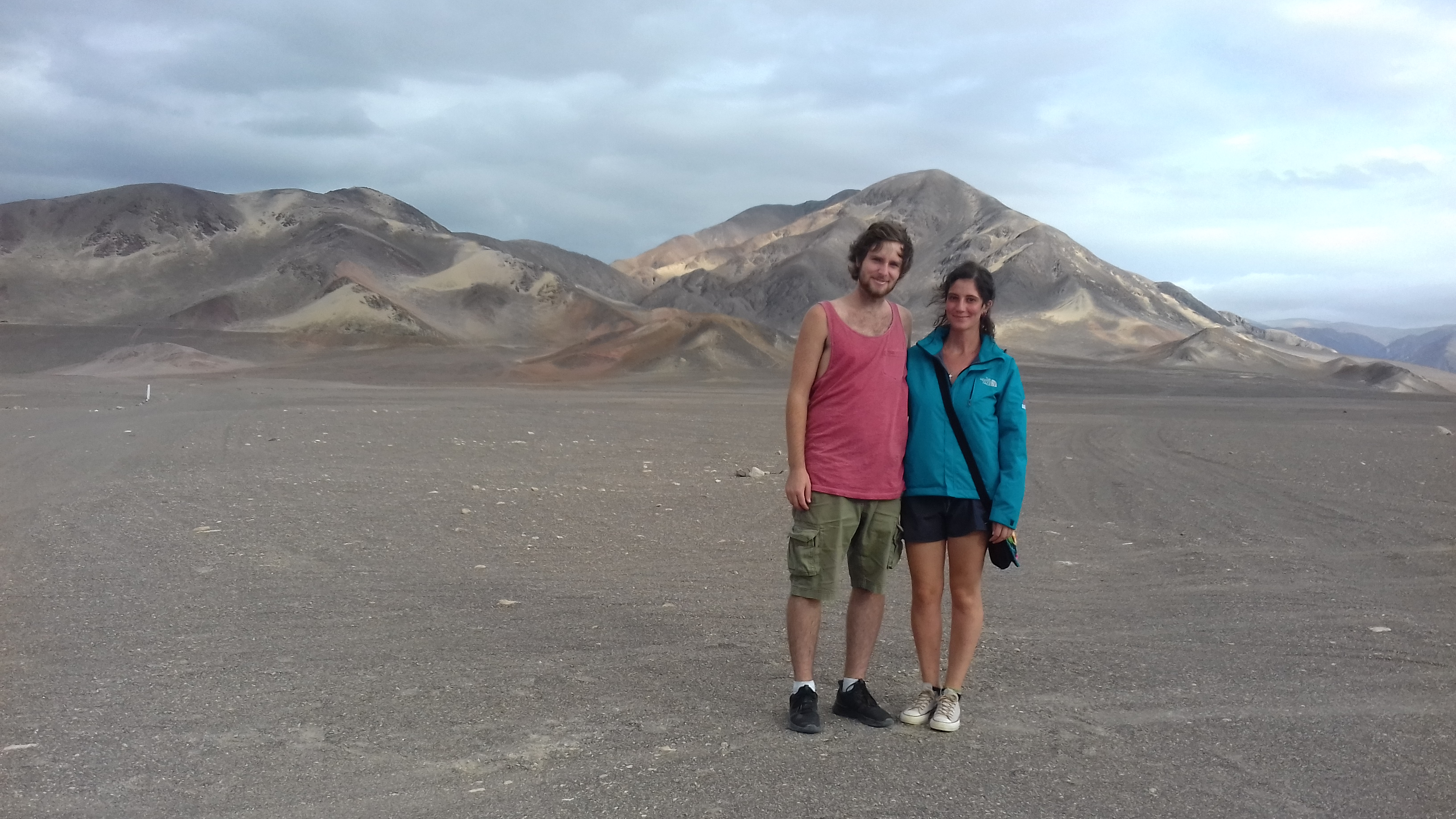 two people standing in front of a mountain