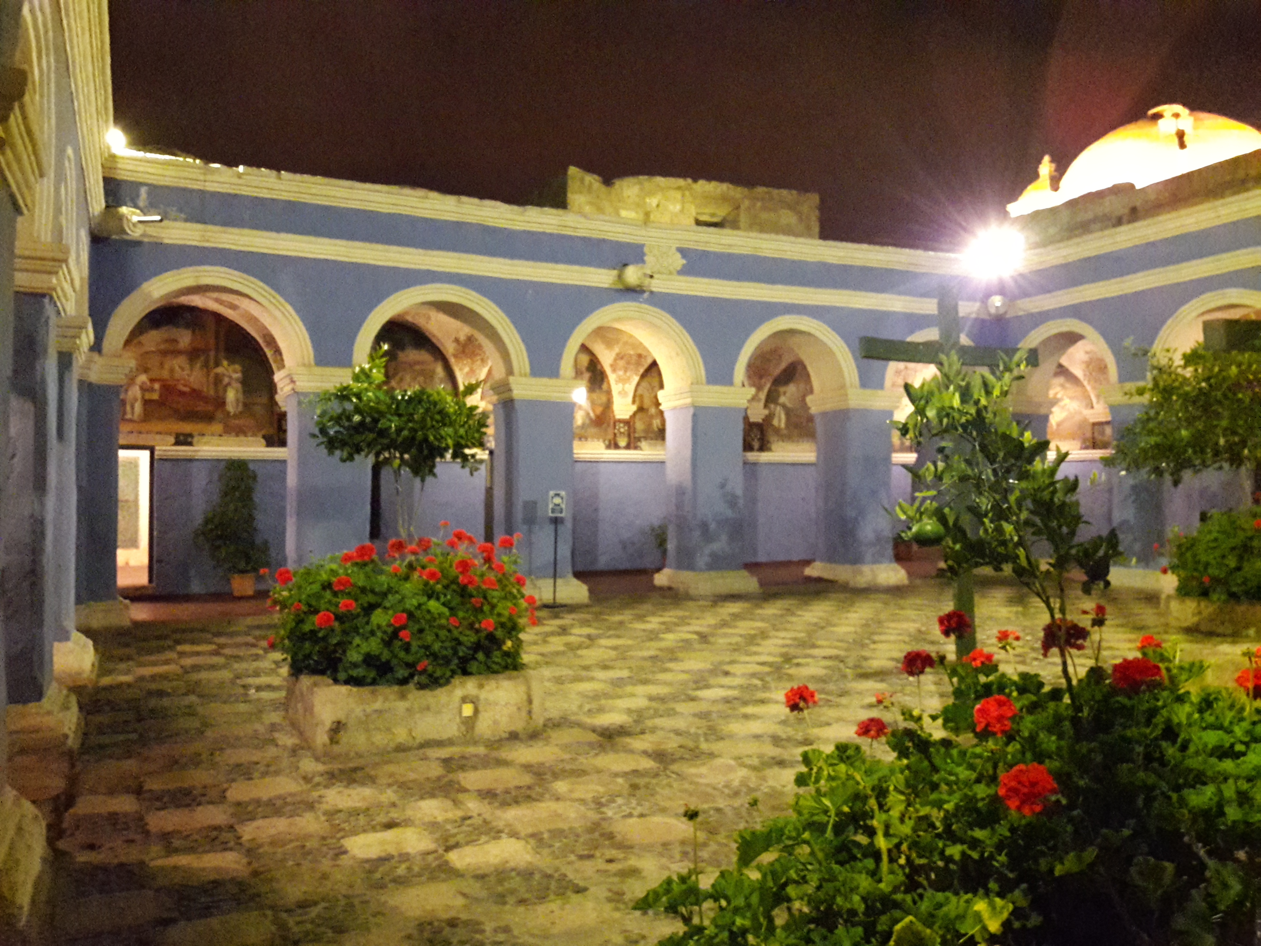 Blue archways. Flower pots with red flowers