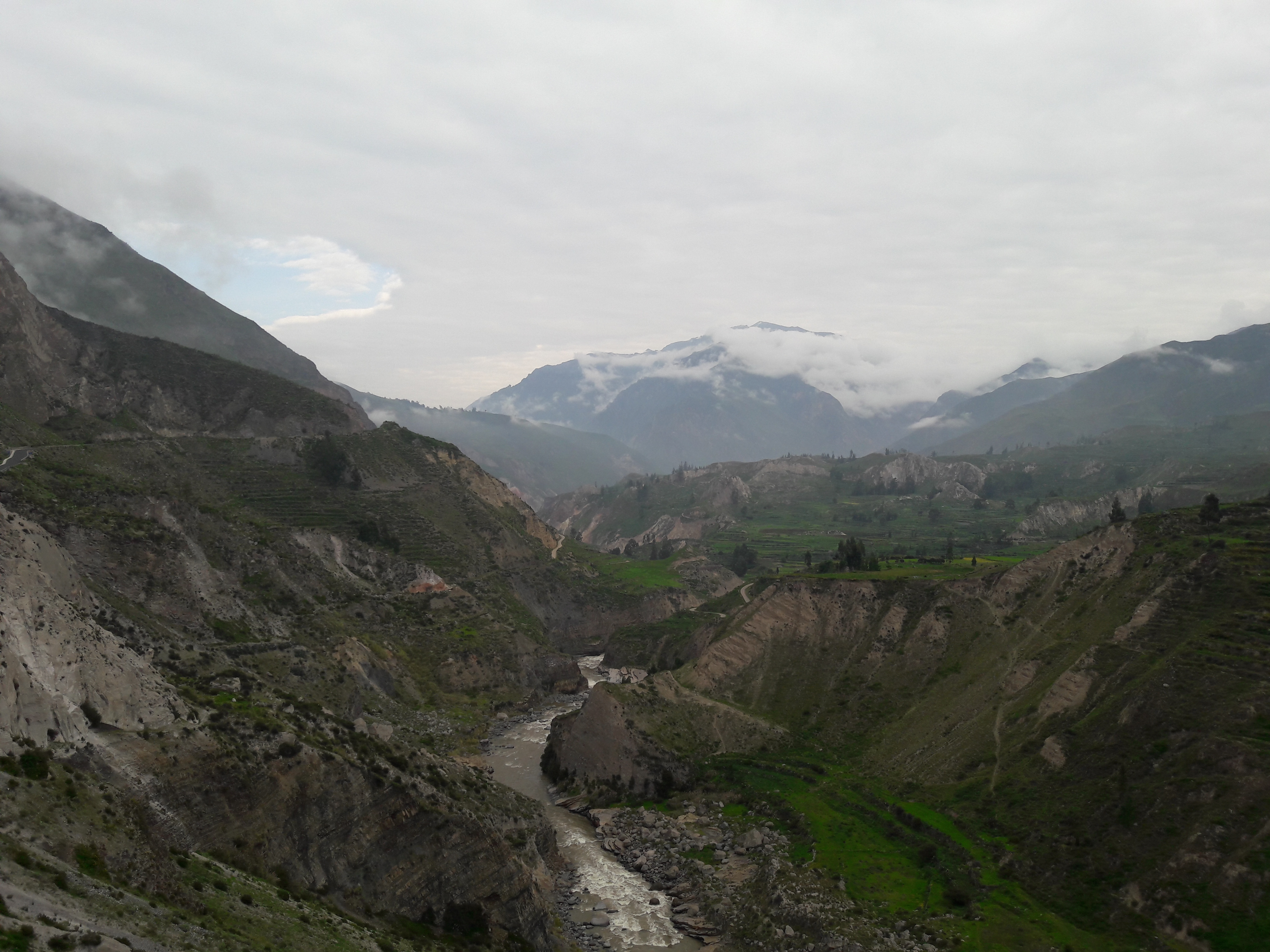 A valley with a river and a cloudy sky