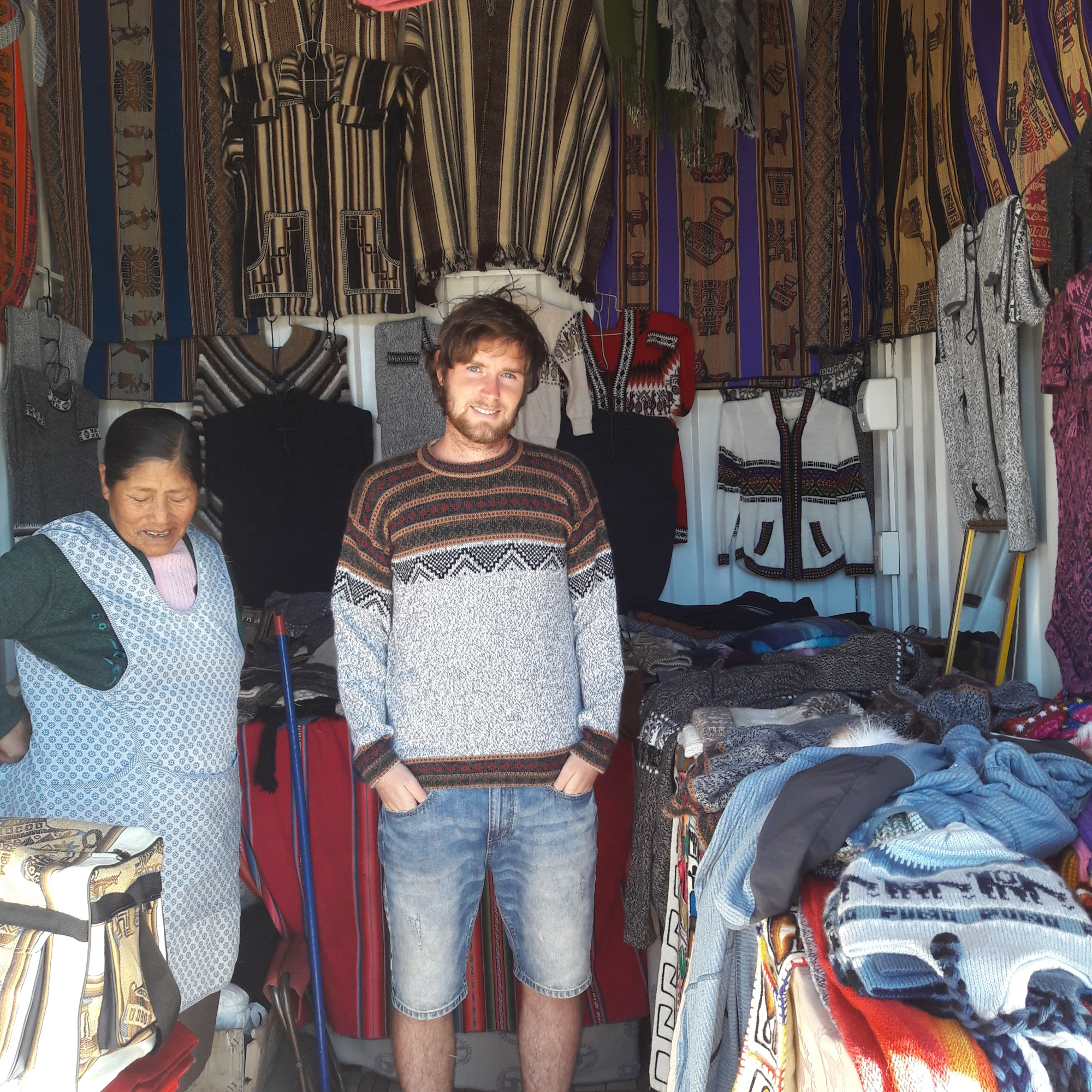 A man standing in a market. A woman on the side.