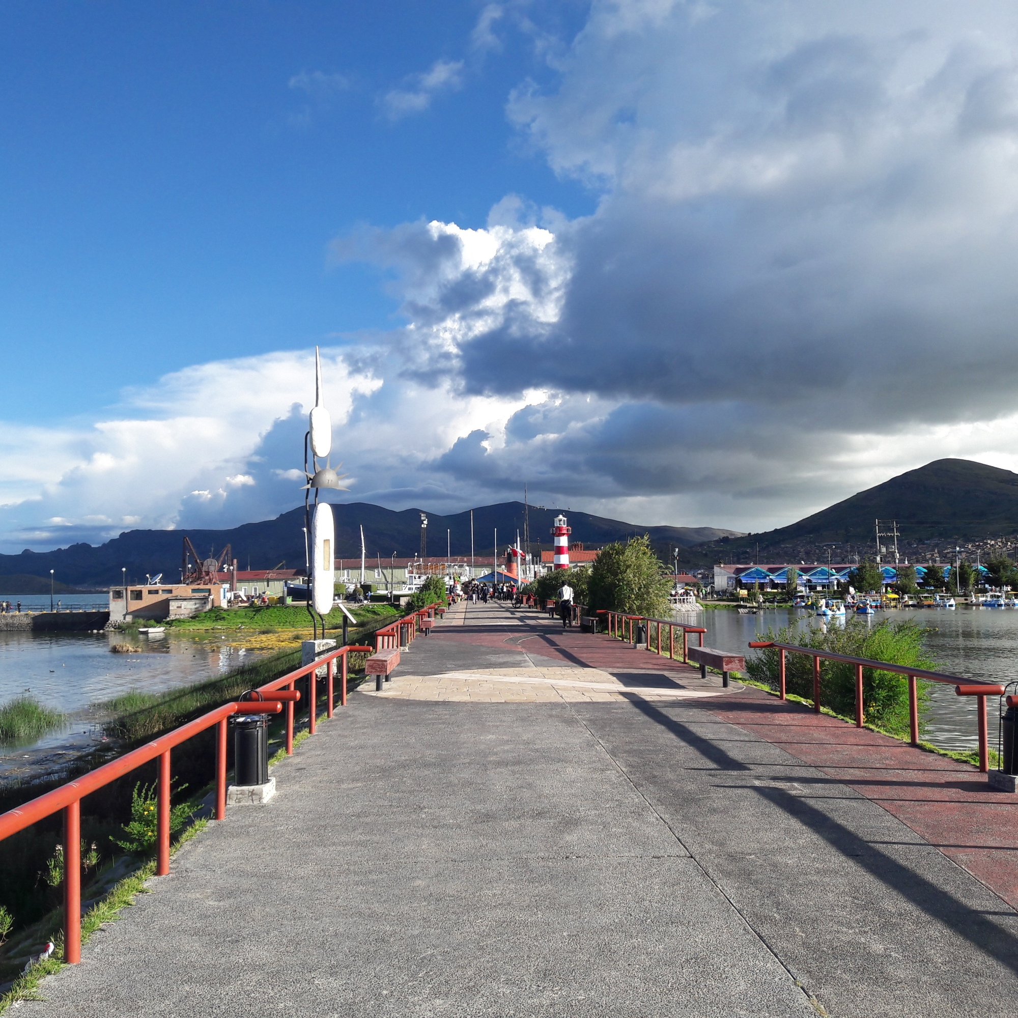 A street with mountains in the background. A lake both sides. the sides.