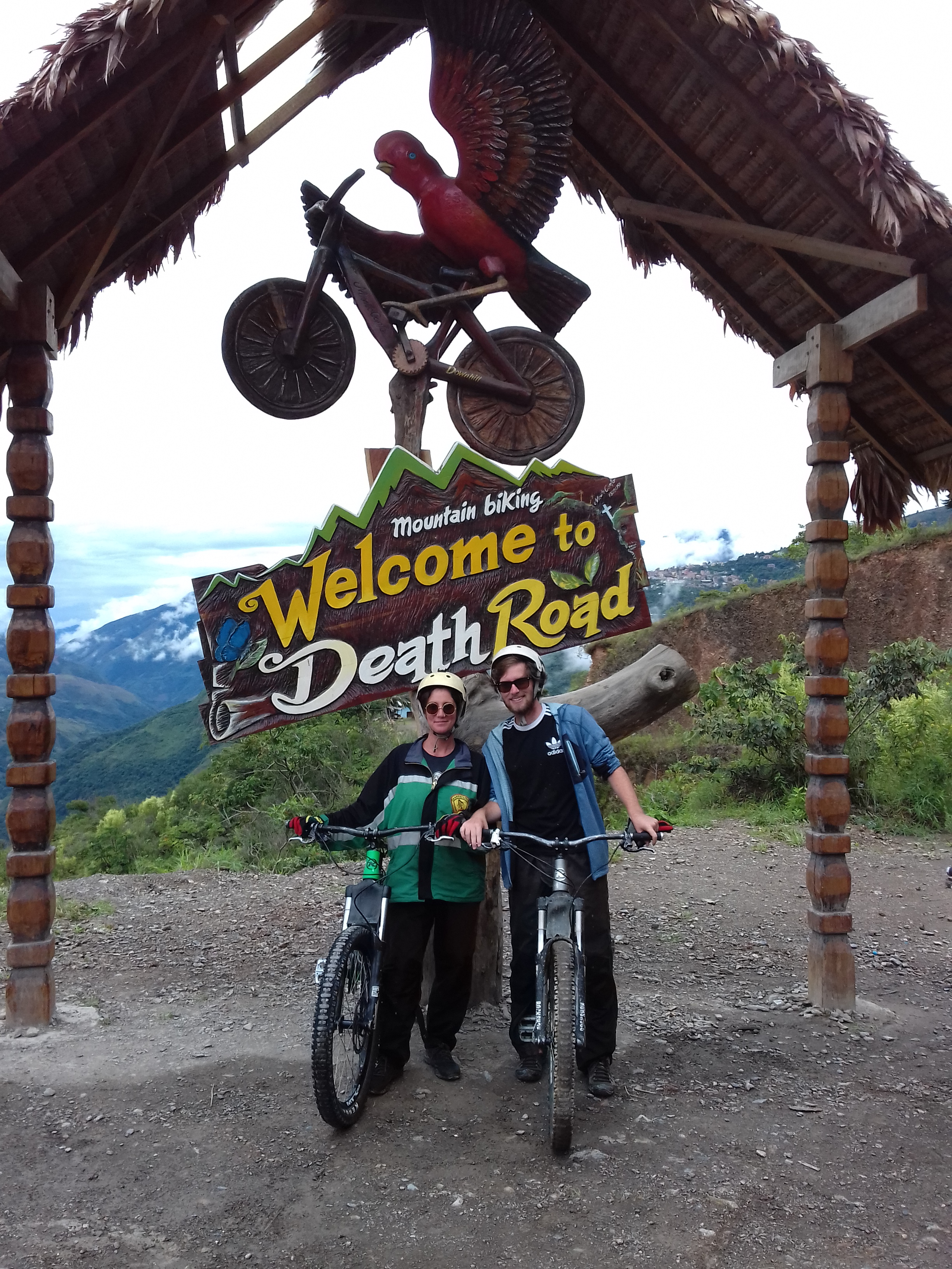 Two people on a bike standing in front of a sign