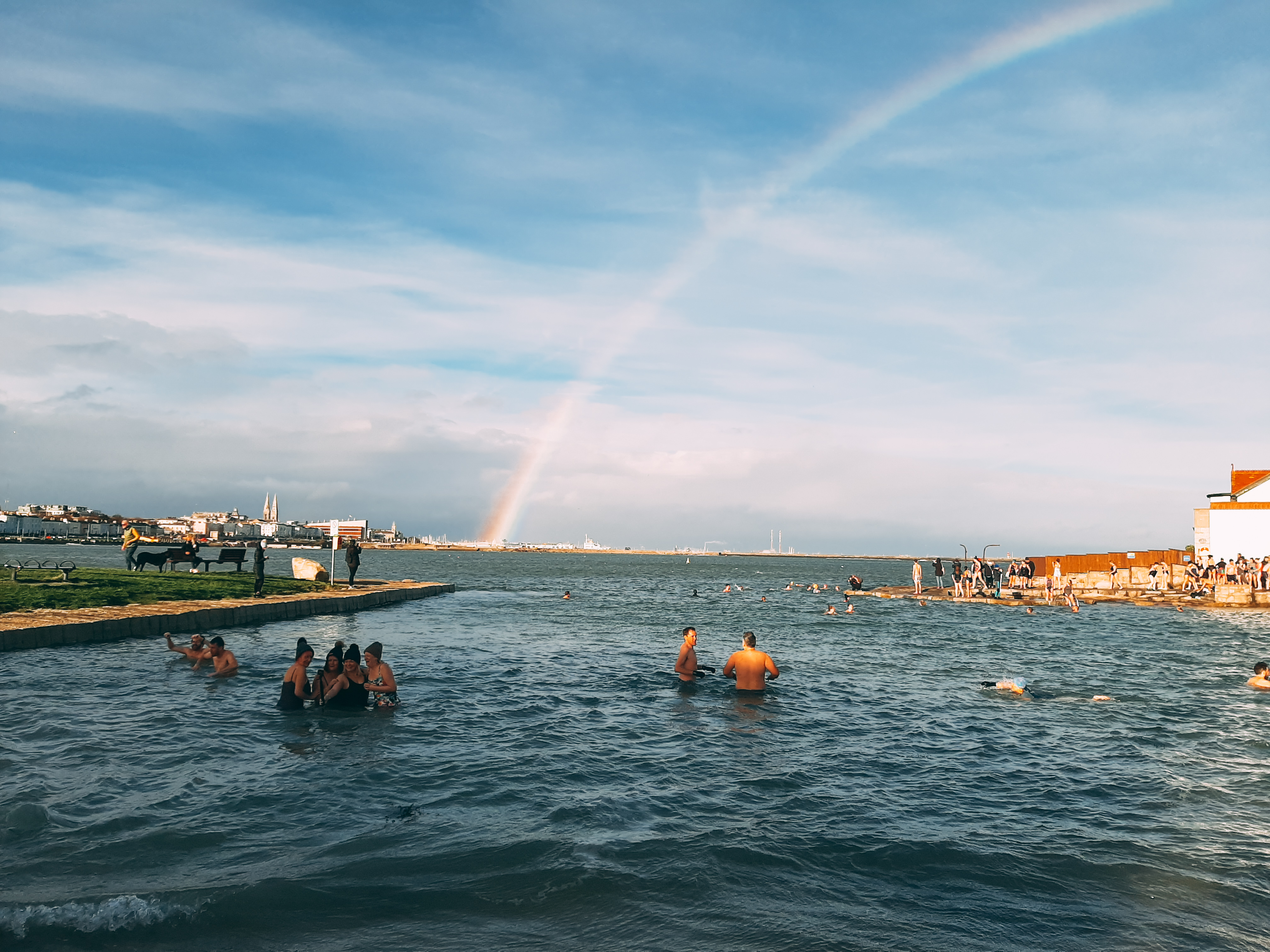 People swimming in a body of water. A rainbow in the sky