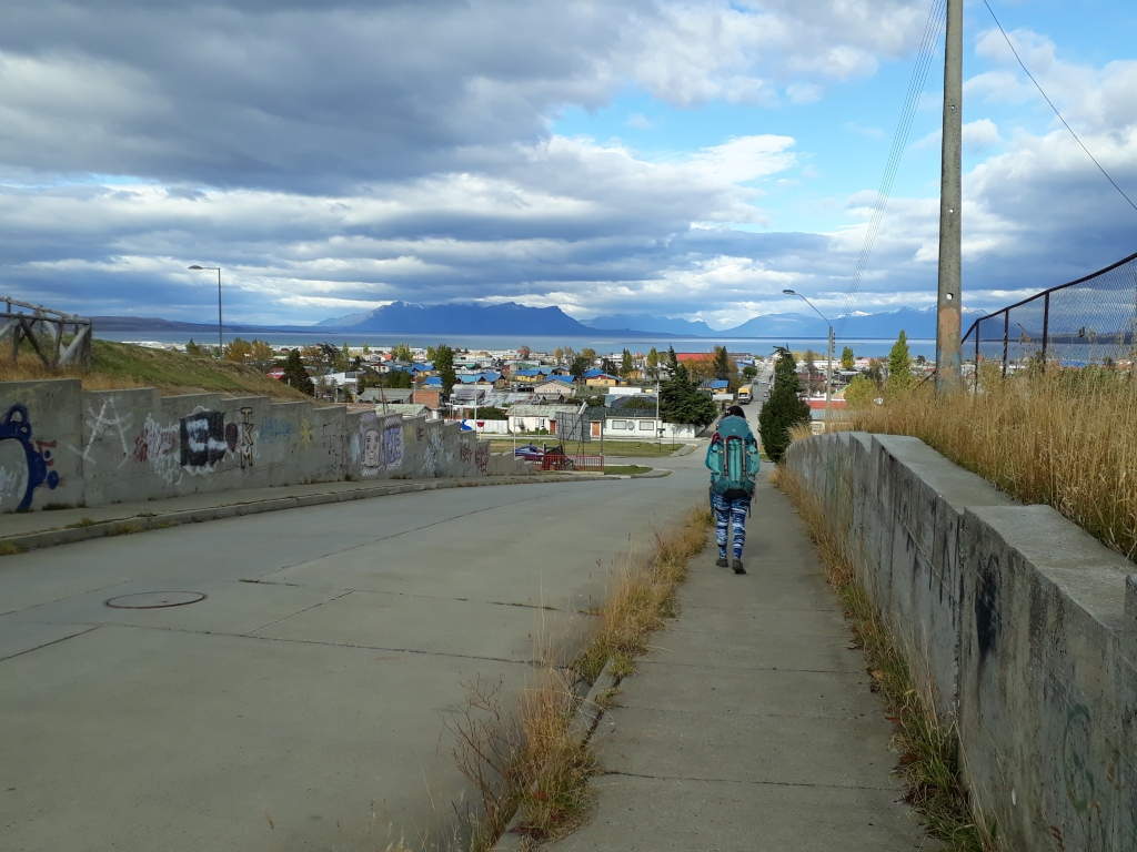 Someone walking with a backpack. Houses and mountains in the background.