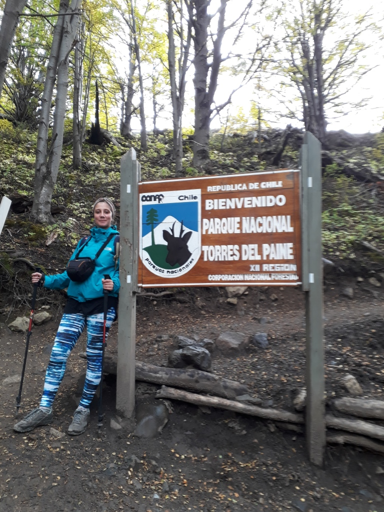 "A woman standing next to a sign in a wood saying ""Bienvenido Parque Nacional Torres del Paine"""